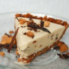 Peanutty Ice Cream Pie - Softened vanilla ice cream is mixed with coconut and chopped peanuts and spread into a chopped peanut crust, then frozen until firm for a rich and creamy dessert pie. Top with M&Ms®, sprinkles, toasted coconut, or chocolate shavings before serving.
