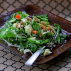 Winter Green Salad - A colorful combination of hardy greens, avocado, pear, walnuts, and raisins is tossed with a flavorful vinaigrette dressing for a healthful and hearty salad.