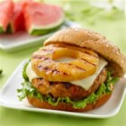 Teriyaki Pineapple Turkey Burgers from DOLE(R) - Ground turkey burgers with a hint of fresh ginger and teriyaki sauce are grilled and served on buns with grilled pineapple and a slice of Cheddar.