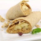 Emmi's Banana Wraps - These fun breakfast banana wraps are so easy a kid can help make them. Whole wheat tortillas are spread with peanut butter and filled with a banana half, coconut, and crunchy granola cereal.
