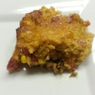 Pork Tamale Pie - Roast pork is combined with a creamy and spicy cornmeal and tomato mix, and then baked until golden brown. Top with shredded cheese.