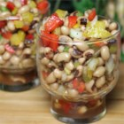 Marinated Black-Eyed Pea Salad - Diced red and yellow bell peppers, jalapeno chiles, onion, garlic, and parsley are tossed with black-eyed peas and crumbled bacon in a colorful salad seasoned with a tangy balsamic and red wine vinegar, cumin, and olive oil dressing.