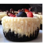 Mini Cheesecakes from PHILADELPHIA(R) - Mini cheesecakes topped with whipped cream, blueberries, and lemon zest make elegant little individual desserts.