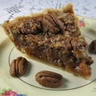 Kentucky Pecan Pie - Corn syrup and brown sugar do magical things in this simple pecan pie that bakes up rich, gooey and delicious. The filling is stirred up, poured into an uncooked pie shell, sprinkled with pecans and baked.