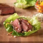 Inside-Out Grilled Steak Salad - Strips of lightly-seasoned grilled steak on top of tender lettuce leaves with assorted colorful vegetables, a light dressing, and optional goat cheese and nuts make a hearty and colorful salad.