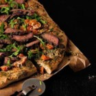 Pesto Steak and Arugula Pizza - The bold, robust flavors of grilled beef top sirloin slices are a sensational topping on a tomato and arugula pizza.