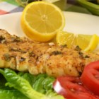Grilled Cod - Firm white cod fillets are seasoned with Cajun spice mix and lemon pepper before being grilled over hot coals. A lemon-butter sauce is basted onto the fish as it cooks.