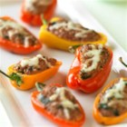 Beef and Couscous Stuffed Baby Bell Peppers - Spinach, couscous, and ground beef fill colorful mini peppers that are baked with a cheese topping for a pretty and flavorful appetizer.