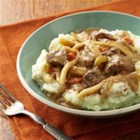 Beef and Noodles over Skin-On Mashed Potatoes - Slowly simmered beef broth with herbs and veggies is simmered until beef is tender, then served with egg noodles over mashed potatoes.