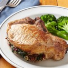 Spinach-and-Mushroom-Stuffed Pork Chops - Pork chops are stuffed with a spinach, mushroom, tart cherry, and Parmesan mixture, then browned in butter and baked for a delicious dinner that's perfect for a special occasion.