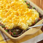 Cheesy Shepherd's Pie - Browned ground beef with carrots, peas, and onions in a creamy sauce is topped with mashed potatoes, baked until hot, then topped with shredded Cheddar cheese.