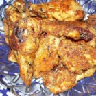 Garlic and Parmesan Chicken Wings - The trick to keeping these oven-baked chicken wings crispy, is parboiling the wings in a flavorful liquid, which helps season the chicken and produce a surface texture in the oven that your guests will swear came straight out of a deep fryer.