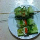 Mini Cucumber Sushi Rolls - Thin cucumber slices are rolled around shredded carrot, cream cheese, and raisins for a little sushi-shaped finger food that's tied with a fresh chive.