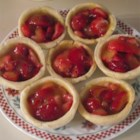 Strawberry Tarts - This easy recipe makes twelve miniature tarts, the perfect offering for a tea party. A cooked apple glaze is brushed over the bottom of each pre-baked tart shell. Sliced strawberries are spooned in and more apple glaze is poured on. The tarts are chilled and served with a dollop of whipped cream.
