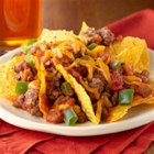 Spicy Beef Nacho Bake - Browned ground beef and diced jalapeno peppers combined with chunky salsa is topped with chips and cheese, and baked until cheese is melted for this quick, spicy dish.