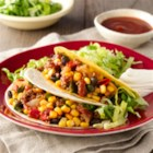Taco Dinner - Ground beef tacos with beans and veggies are seasoned just right, served in tortillas or tacos--and they're ready in under half an hour.