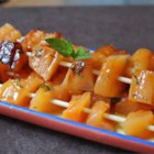 Skewered Cantaloupe - Chunks of cantaloupe are threaded onto skewers and brushed with honey butter and chopped mint. It makes a terrific grilled side dish, or, for dessert, serve it with big scoops of vanilla ice cream.