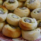 Pesto Sausage Biscuit Bites - Biscuit dough is lined with pesto and rolled around sausage links for a tasty and crowd-pleasing appetizer that will disappear quickly.