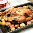 Roasted Herb Chicken and Potatoes - Arrange the potatoes, onions, and whole chicken in a pan, season with a piquant Kikkoman Soy Sauce mixture, and let the oven do the rest!