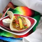 Colorful Vegetable Fajitas - Eat your veggies! No problem doing that with these fabulous fajitas. Summer squash, red and green peppers and strips of red onion are sauteed with oil and garlic and then wrapped into a warm tortilla. A sprinkling of cheese and cilantro and your on your way.