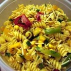 Restaurant-Style Santa Fe Pasta - Chill this colorful, spicy salad the day before you serve it. Toss rotini pasta with tomato juice, olive oil, vinegar, chili powder, and paprika, then add a festive mix of red and green bell peppers, corn, cilantro, scallions, Parmesan and chicken.