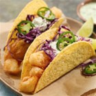 Beer Battered Fish Tacos - Crispy taco shells filled with Mexican beer-battered fish are topped with shredded red cabbage, chimichurri aioli and fresh jalapenos.