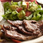 Bison Fajitas with Guacamole Salad - Strips of bison flank steak are quickly stir-fried with bell peppers, onion, and jalapeno and served hot on tortillas with salsa, sour cream, and guacamole.