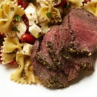 Caprese Bison Sirloin Steak with Bow Tie Pasta - The delicious flavor of freshly cooked bison steaks pairs beautifully with traditional Italian caprese ingredients like basil pesto, fresh mozzarella cheese, and sweet grape tomatoes.