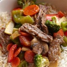 Sizzling Bison Steak Stir-Fry - Thinly sliced bison ribeye steaks and veggies are stir fried, mixed with an Asian-inspired ginger sauce, and served with hot brown rice.