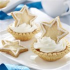 Superstar Eggnog Tart - Pretty eggnog-flavoured custard tarts are decorated with iced stars and whipped topping for a festive treat.