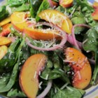 Peach Salad with Raspberry Vinaigrette - This peach salad recipe includes spinach, almonds, and Asiago cheese tossed in a raspberry vinaigrette for a colorful and refreshing starter or side salad for a summer meal.