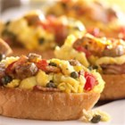 Breakfast Bruschetta - Scrambled eggs, chunks of sausage, chopped bacon, and briny capers make a delicious gourmet breakfast bruschetta.