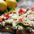 Individual Greek Pita Pizzas - Pita bread is topped with a Greek-inspired spinach salad with olives, feta cheese, and mozzarella cheese. A lemony dressing completes this vegetarian pizza.
