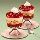 Strawberry White Chocolate Trifle - These pretty layered trifles with strawberry pie filling, crumbled sugar cookies and white chocolate mousse are topped with a dollop of whipped cream.