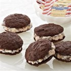Peppermint Chocolate Sandwich Cookies - Handcrafted chocolate cookies are sandwiched around a filling of creamy peppermint icing for a beautiful holiday treat.