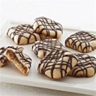 Sugar Cookies with Caramel Pockets and Chocolate Drizzle - They'll rave when you bring out a tray of these beautiful cookies with chocolate caramel candy centers and a drizzle of chocolate.