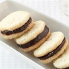 Cream Cheese Sandwich Cookies with Dark Chocolate Filling - Creamy dark chocolate is sandwiched between rich sugar cookie rounds.