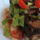 Chef John's Garlic-Studded Roast Pork - Pork shoulder roasted with plenty of garlic is sliced, pan-fried, and served over white beans with romaine and tomato salad for a gourmet take on a budget cut.