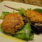 Deviled Crab Cakes on Mixed Greens with Ginger-Citrus Vinaigrette - Fresh, lemon-scented crab cakes are pan fried to golden brown and served on top of mixed greens with a tangy vinaigrette and avocado slices in this elegant appetizer dish.
