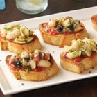 Contadina(R) Mediterranean White Bean Bruschetta - Slices of baguette are topped with pizza sauce and a chunky bean spread then topped with lemon zest and parsley for quick and tasty party appetizers.