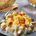 Cheesy Chicken and Potato Casserole with Bacon - Frozen hash browns with onions and peppers are topped with cooked chicken, a delicious soup mixture and Cheddar cheese. Baked until hot and bubbling and sprinkled with crumbled bacon, this savory, satisfying casserole is sure to please.