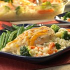 Easy Baked Chicken and Rice Casserole - 15 minutes is all you need to put together this scrumptious one-dish casserole! Tender chicken breasts sit on top of a bed of creamy rice with broccoli and carrots. Topped with melted Cheddar . . . dinner is served!