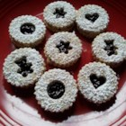 Raspberry Linzer Cookies - Raspberry jam is sandwiched between two sugar cookies and topped with a sprinkling of confectioners' sugar for a delightful cookie treat.