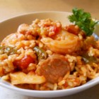 Oven Baked Jambalaya - A sixteen-serving batch of Creole classic! Chicken, ham, shrimp, and andouille sausage are combined with onion celery, green pepper and garlic. Tomatoes, chicken stock and rice are stirred in, and the whole thing is baked in a large roasting pan.