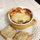 Rich and Simple French Onion Soup - A slice of French bread layered with three varieties of cheese is broiled on top of individual servings of this soup of Spanish onions cooked in beef bouillon to form a rich crust.