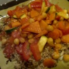 Israeli Moroccan Couscous - Carrots, turnips, sweet potatoes, zucchini and red bell pepper are simmered with garbanzo beans and tomato sauce, and flavored with cinnamon, turmeric and curry.  This beautiful, tasty concoction is served atop hot couscous.