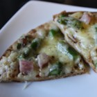 Pizza with Ham, Asparagus, and Ricotta - Top homemade pizza crust with a white sauce made from ricotta cheese and olive oil, smoked ham, asparagus, white Cheddar, and Parmigiano-Reggiano cheese.