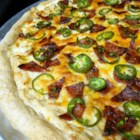 Jan's Jalapeno Popper Pizza - A cream cheese base replaces tomato sauce in this pizza topped with bacon and jalapeno peppers to bring poppers to pizza.
