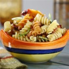 Tri-Color Rotini Pasta Salad with Peaches and Basil - Chopped grilled peaches, celery, green onions, and crumbled bacon are tossed with tri-color rotini and a basil-curry dressing for a sensational pasta salad.