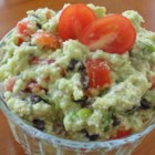 Cheesy Black Bean Guacamole - Nearly equal amounts of cheese, black beans, tomato, and avocado, spiced with cayenne, make a great twist on traditional guacamole.